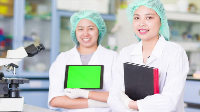 Scientist showing her digital table with a green screen video