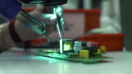Scientist Soldering Pads On The Device video