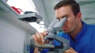 Scientist student working with microscope. Male scientist looking microscope video