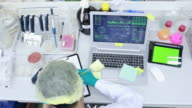 Scientist using on a computer, microscope and molecule model. video