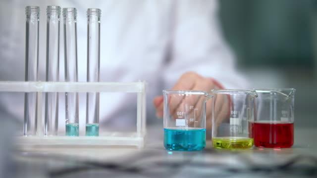 Scientist working with liquid in laboratory glassware. Test tubes filling liquid video