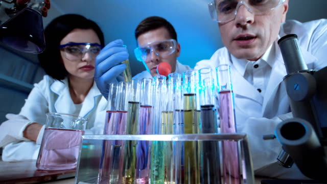 Scientists in lab experimenting with chemicals video