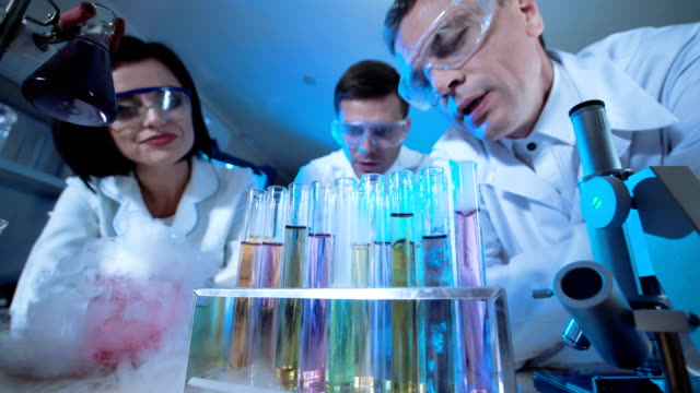 Scientists watching reactions in test tubes video
