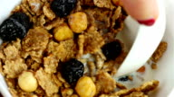 Scooping with a spoon from a bowl with cereal, dried cherries and hazelnuts, slow motion video
