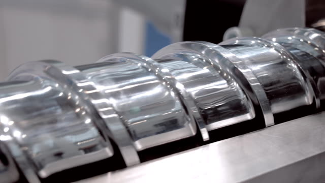 Screw to feeding the plastic pellets to the heater and molds extrusion equipment video