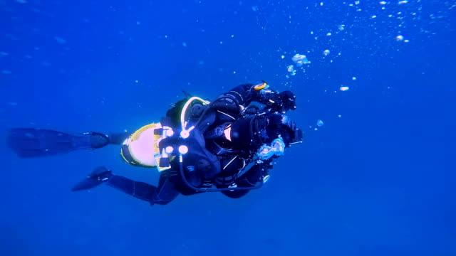 Scuba Diver Descending into Blue Water video
