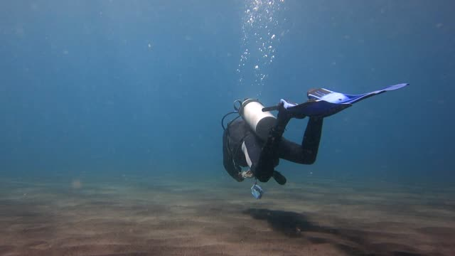 Scuba diver swimming on volcanic sand under sea video