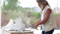Sculptor is creating a sculpture using a hand tool video