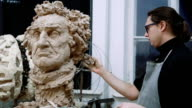 Sculptor modelling sculpture adjusting face details head made of clay video