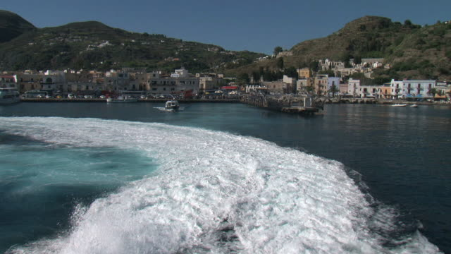 Scummy wake of yacht leaving a small Sicilian harbor video