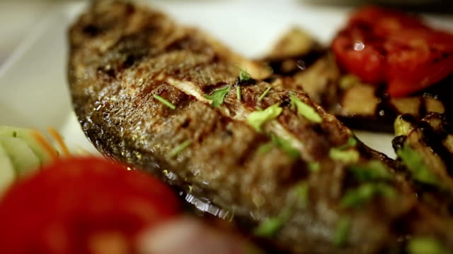 Sea bream fish on the plate arranging on a plate video
