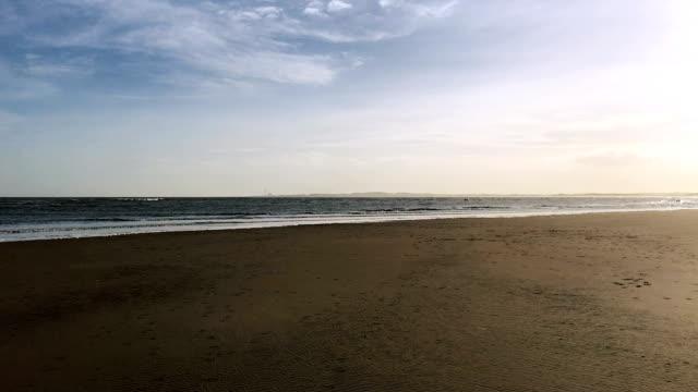 Sea meets sky horizon, as waves crash on empty beach video