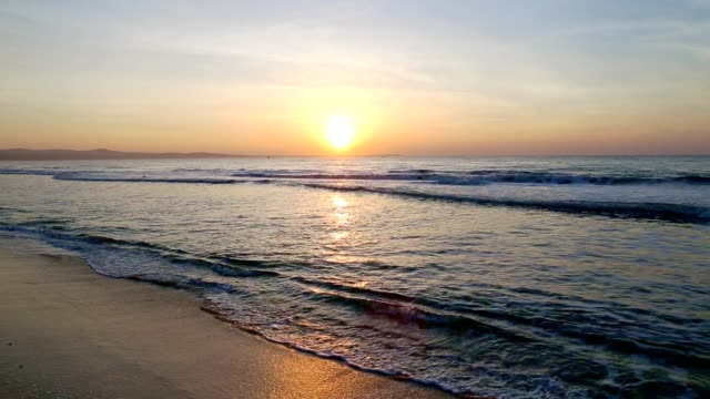 Sea scenery golden sunrise over horison. Dark waves go to sandy beach. Sound of nature. Ocean horizon beautiful background sea scene. Ocean waves blue water shine by sun light morning sunrise video