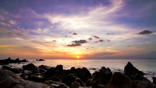 Sea sunset on rock shore pan time lapse video
