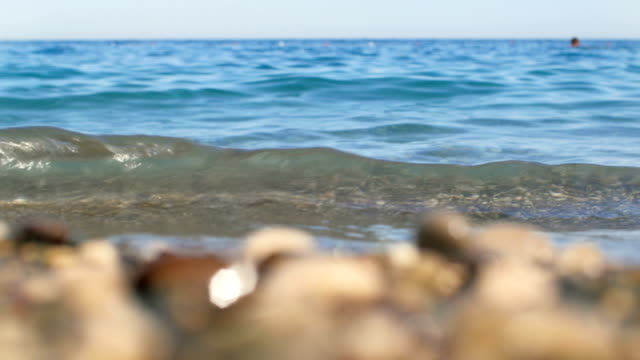 seacoast of Turkey, focus moving from multicolor pebble to blue sea and back, in sunny day video
