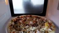 Seafood pizza with shrimp mussels and olives heating in microwave oven video
