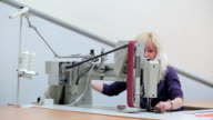 Seamstress puts the cloth into the sewing machine video