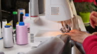 Seamstress Sews Clothes with her Over Lock Machine video