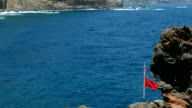Seascape with broken red flag moved by the wind. video