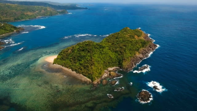 Seascape with tropical island, beach, rocks and waves. Catanduanes, Philippines video