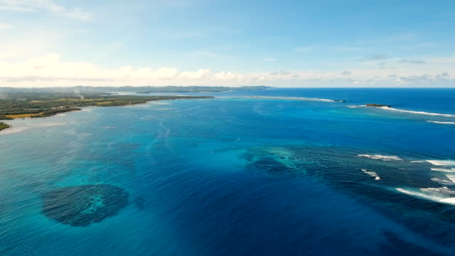 Seascape with tropical island, beach, rocks and waves. Siargao, Philippines video