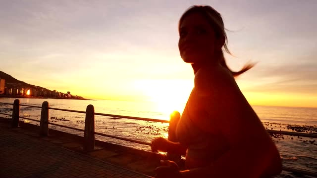 Seaside promenade with active runners training in sunset video