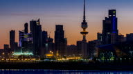 Seaside skyline of Kuwait city from night to day timelapse video