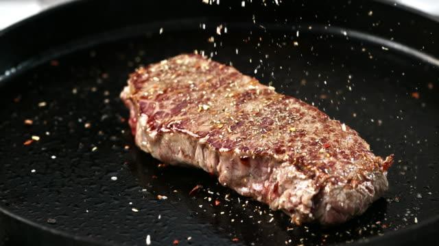 SLO MO Seasoning a pan fried beef steak video