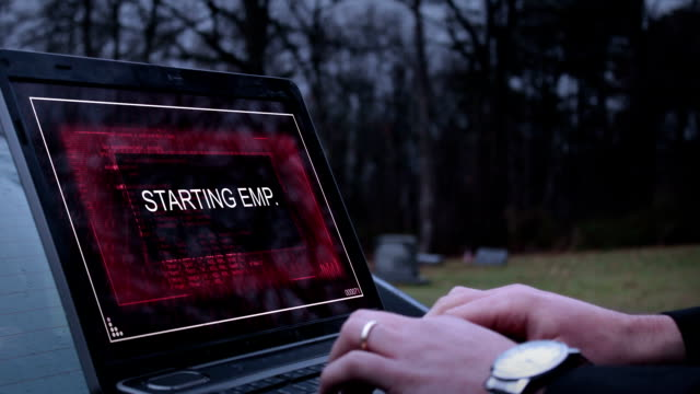 A secret agent or operative activates an EMP on his laptop and flees video