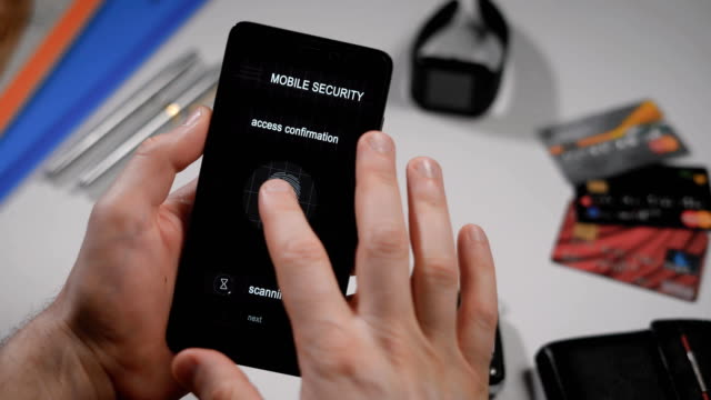 Secure and quick access to your account with fingerprint scanning. The application on the smartphone, the man applies his finger to the scanner, the program allows access video