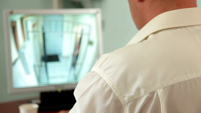 Security guard in control room at CCTV video