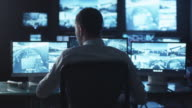 Security officer is drinking coffee while working on a computer in a dark monitoring room filled with display screens. video