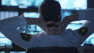 Security officer is relaxing at a computer desk in a dark monitoring room filled with display screens. video