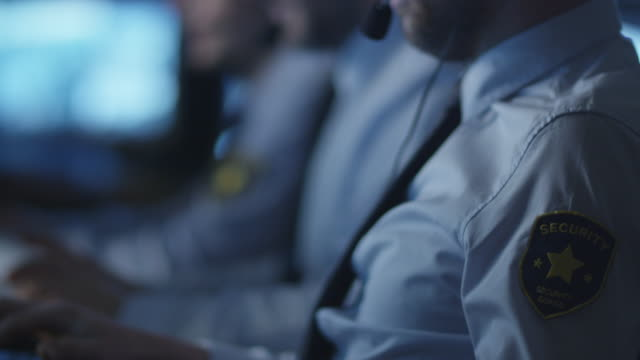Security officer is talking on a headset while working on a computer in a dark monitoring room filled with display screens. video