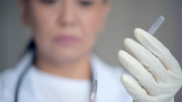 Selective focus of a medical syringe in hands of a professional doctor video