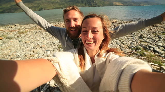 Self portrait of a young couple by the lake shore video