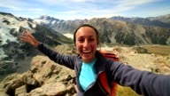 Self portrait of cheering hiker on mountain top, celebrating video