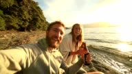 Self portrait of young couple enjoying drink by the lake video