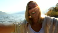 Self portrait of young woman by the lake at sunset video