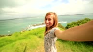 Self portrait of young woman on coastline hill video