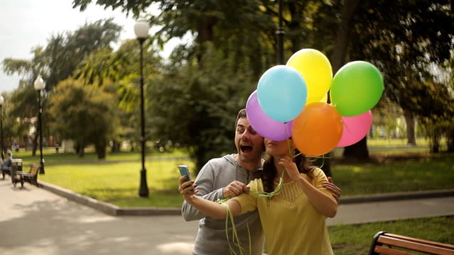 selfie fun loving couple with balloons in the park video