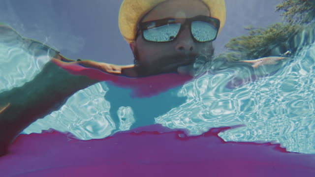 Selfie: man floating in swimming pool with air mattress video
