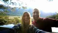 Selfie of young couple in lake mountain landscape video