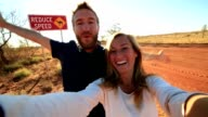 Selfie of young couple standing by Camel warning sign video