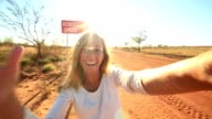 Selfie of young woman standing by Camel warning sign video