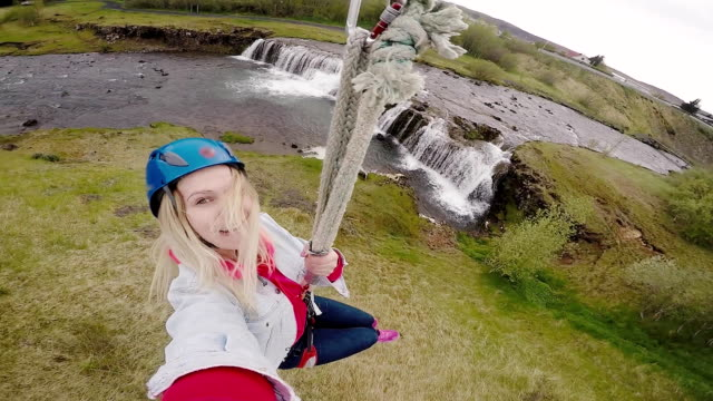 Selfie on action camera of young beautiful woman flying downhill on bungee through the rope way over the river video