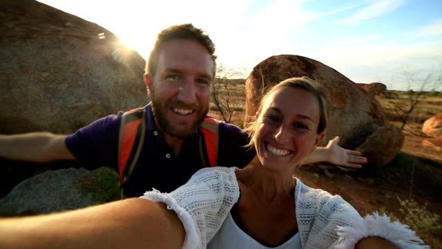 Selfie portrait of two young adults at the Devil's Marbles video