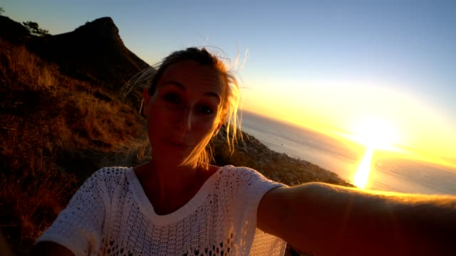Selfie portrait of young woman, mountain and sunset video