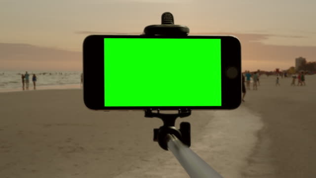 Selfie stick smartphone chromakey green screen Florida beach people video
