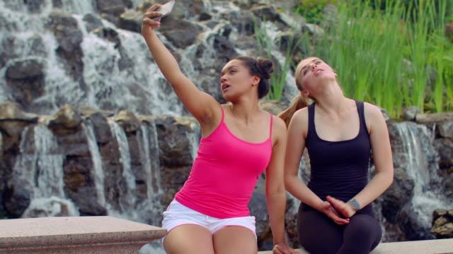 Selfie women. Two young women taking selfie near waterfall. Women selfie video